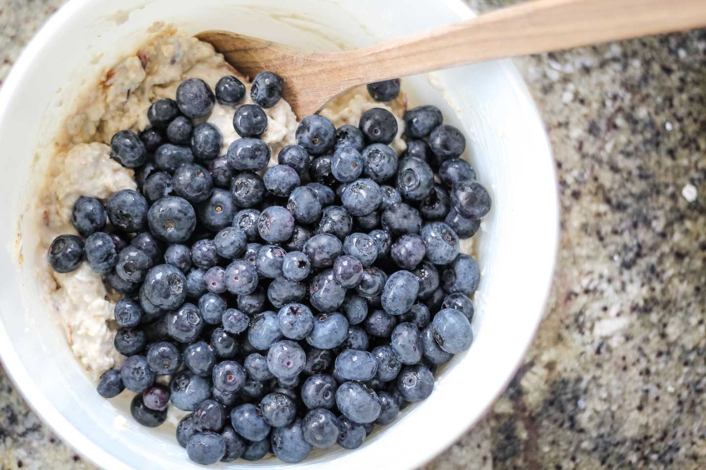 Overhead of a white bowl filled with the overnight oats ingredients (a huge pile of blueberries on the top), being mixed gently with a wooden spoon.