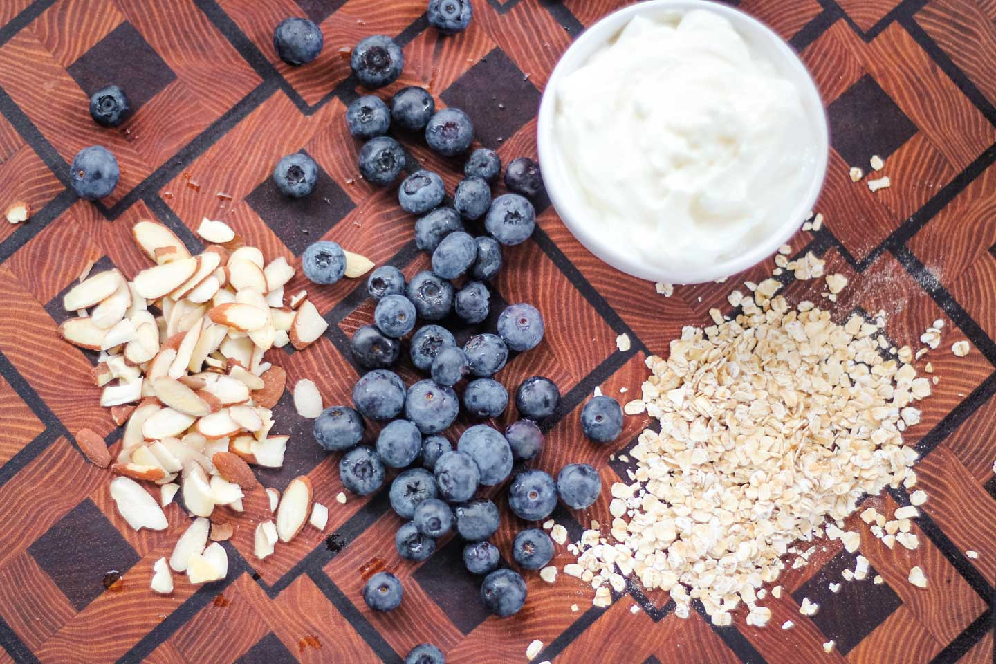 Some of the ingredients for this overnight oats recipe (sliced almonds, blueberries, oats, and Greek yogurt), arranged on a diamond-patterned cutting board, before starting to be mixed all together.