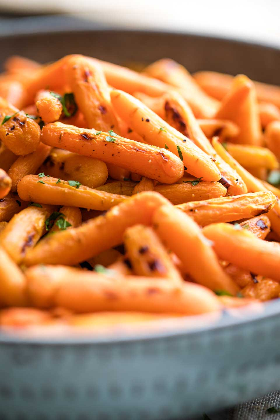 Closeup side view of a blue serving bowl piled with carrots and ready to be served.