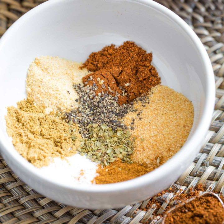 Closeup of a white bowl with the various individual spices that go into this recipe, each in its own little pile in the bowl.