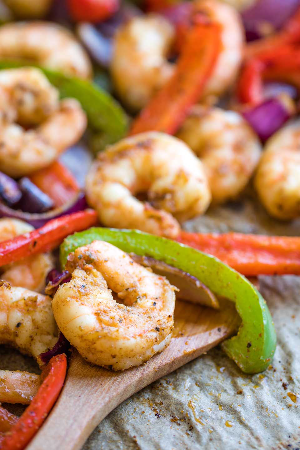 Closeup of a shrimp and some pepper strips after cooking on a parchment, lined sheet pan, so you can see the detail of some of the fajita seasoning.