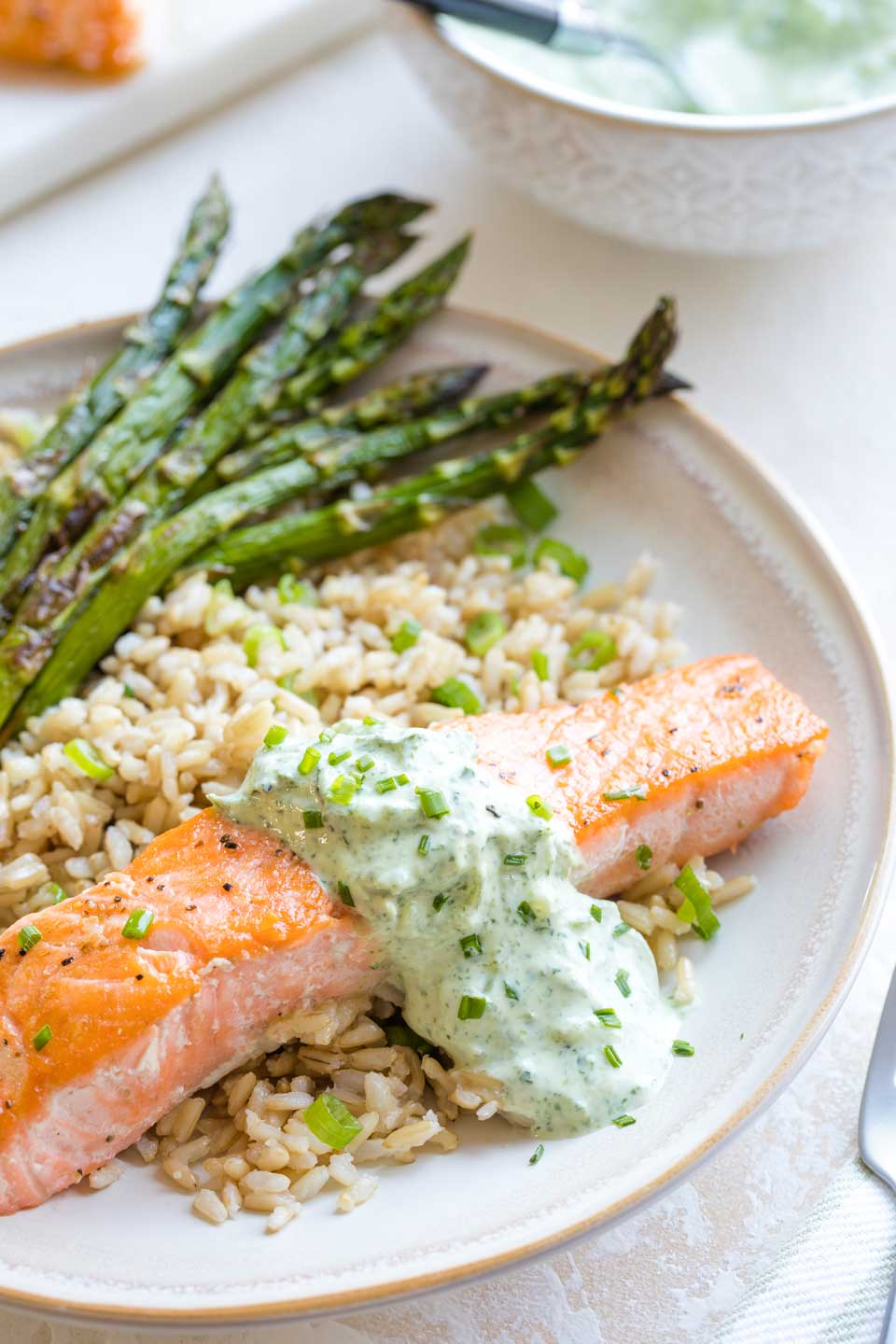 Closeup of the finished recipe, with the pan seared salmon arranged on a rimmed dinner plate, served with rice and asparagus, with utensils and additinal sauce just visible at the edges of the photo.
