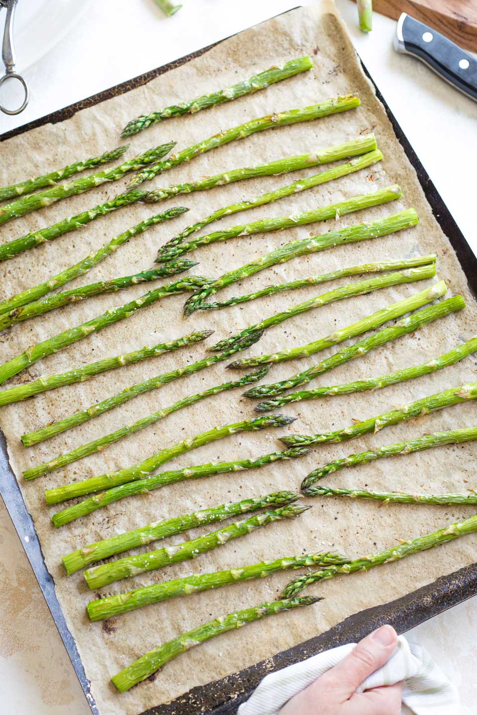 A hand holding the edge of the baking pan just after the asparagus has finished roasting and been taken from the oven.