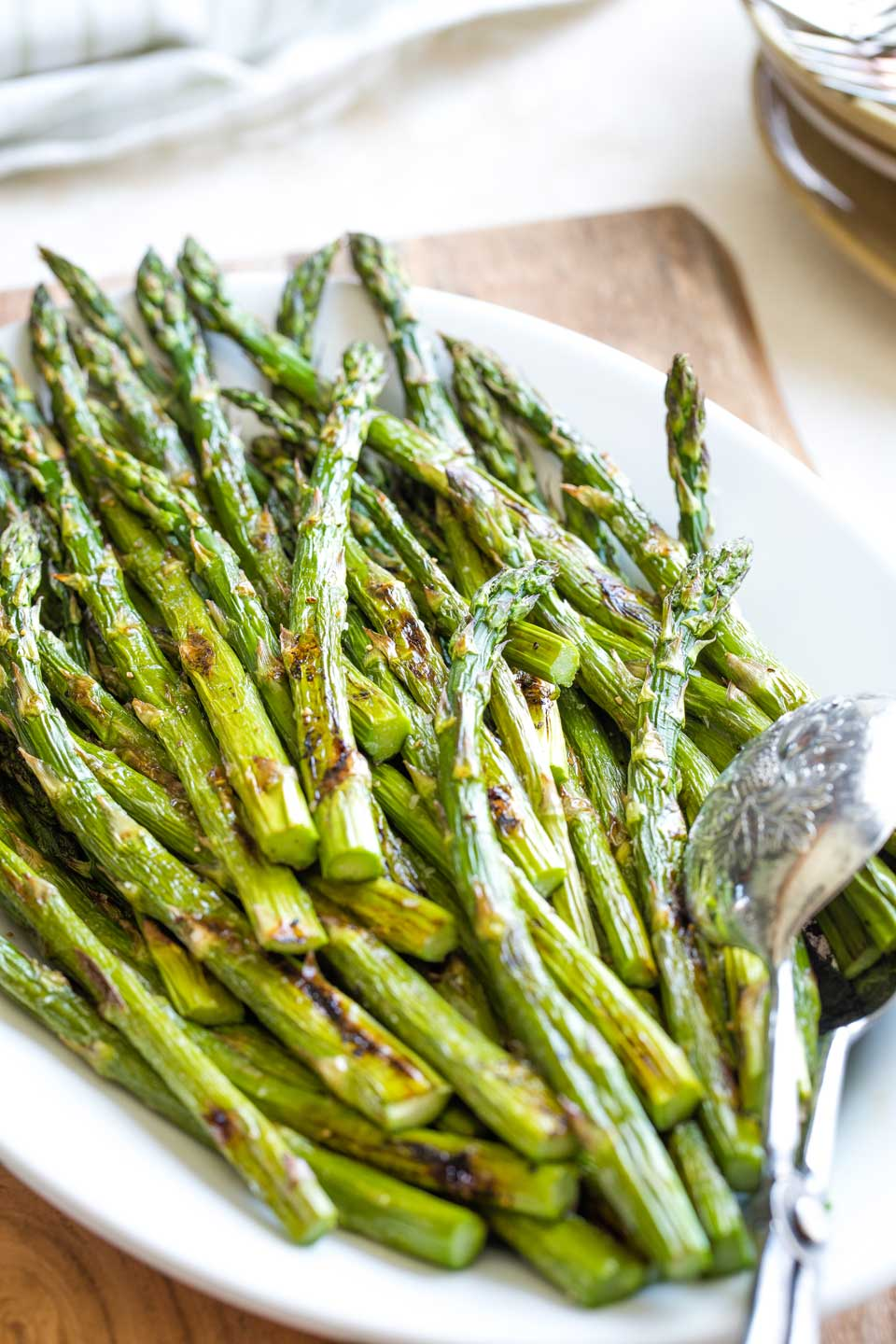 A 3/4 angle shot from the bottom of the asparagus stalks, with the finished stalks piled on a white platter (next to serving tongs) so you can see lots of the brown, roasted spots.