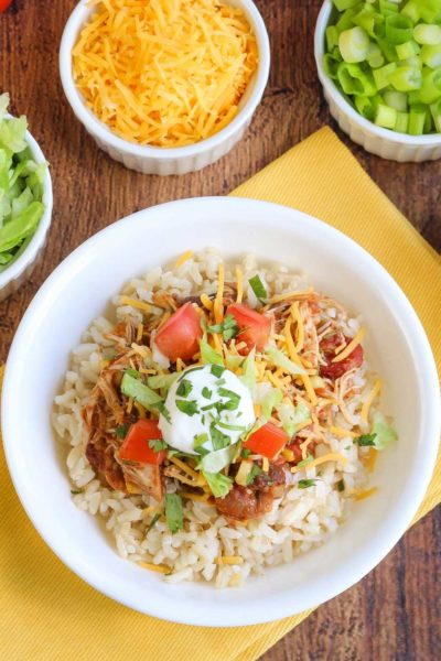 Table set with chicken burrito bowl recipe and toppings in white serving dishes.