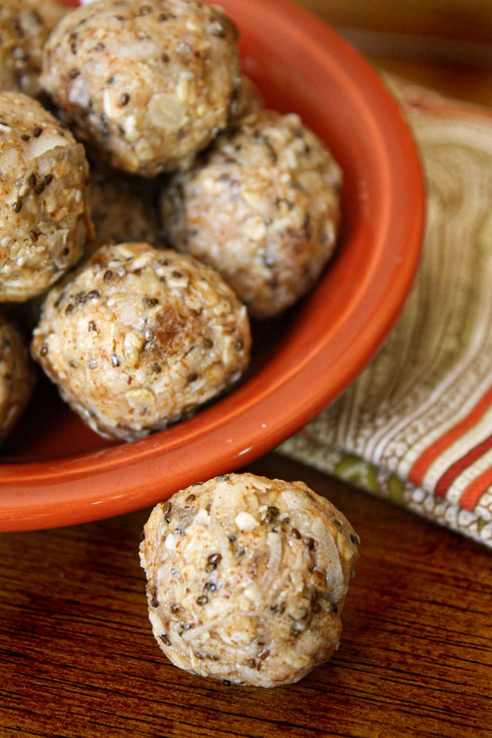 An orange bowl filled with these energy balls, sitting on a decorative napkin, with one ball rolled out in front, onto the wooden table.