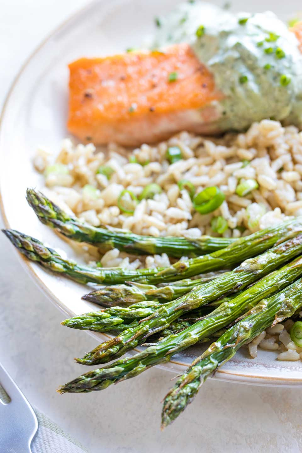 A serving suggestion for this recipe as a side dish, plated on a bed of rice alongside a salmon filet.