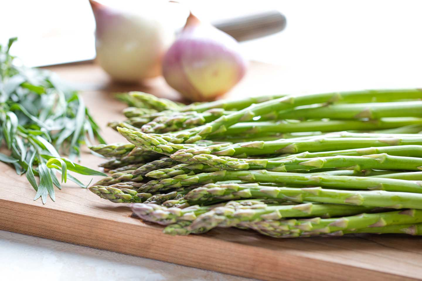 Closeup side view of fresh asparagus spears with herbs, a knife and other vegetables in the background.