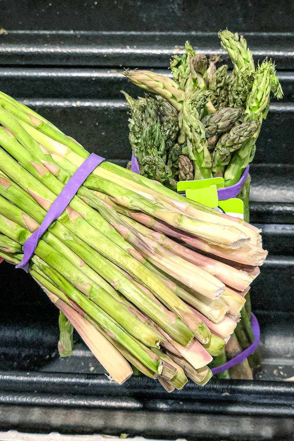 Closeup of the bottom of a bunch of asparagus at the store, showing how the bottoms are wrinkled and dried out.