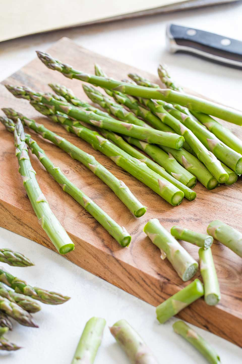 13 asparagus stalks on a wooden cutting board, with the bottom inch or two just sliced off and the discarded ends laying about nearby.