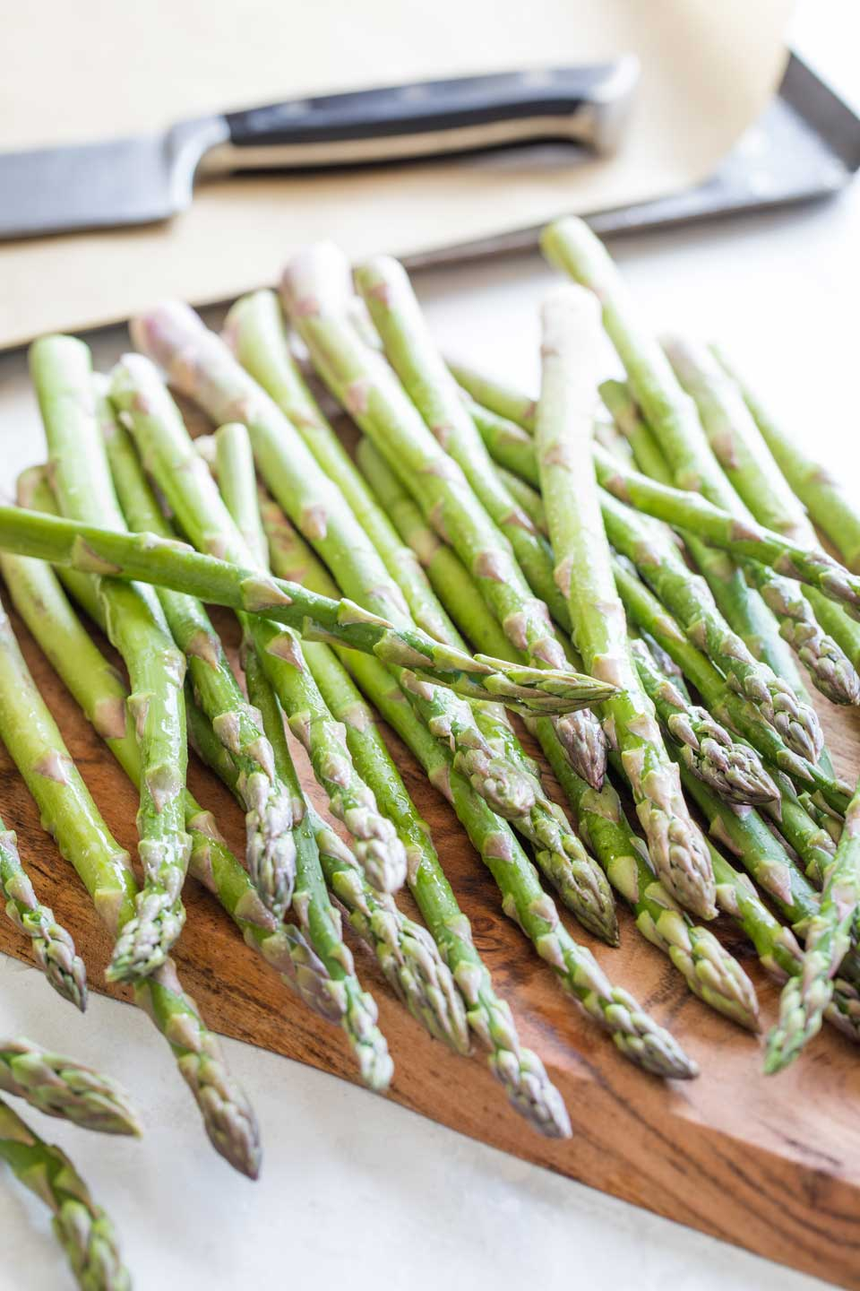 A pound of asparagus, rinsed and rolled across a wooden cutting board with a roasting pan and knife in the background.