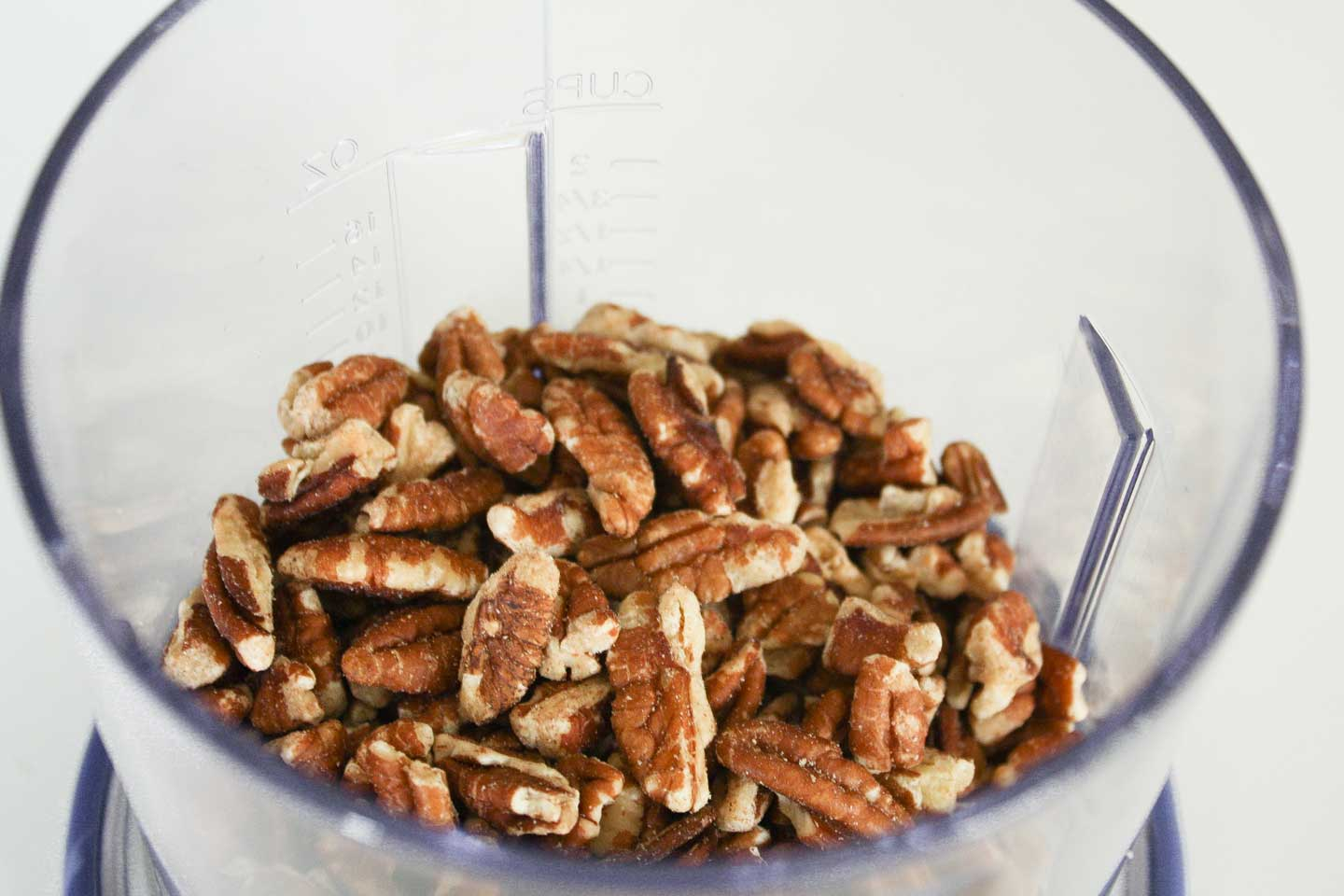 Closeup of the pecans in a mini food processor before being processed to form the pecan butter.