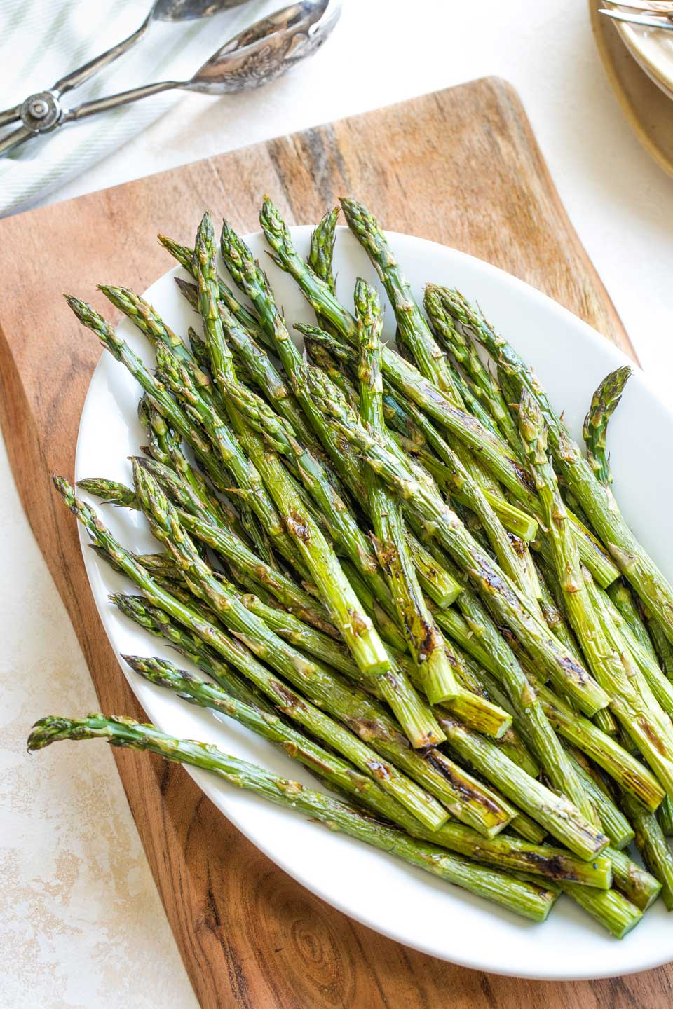Overhead of the full white serving platter loaded with a serving of oven roasted asparagus, with serving tongs and a stack of plates and forks waiting nearby.