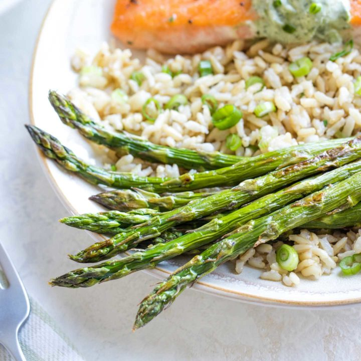 Hero photo of a serving portion of roasted asparagus spears served with rice and salmon, with a green-striped napkin and fork visible alongside.