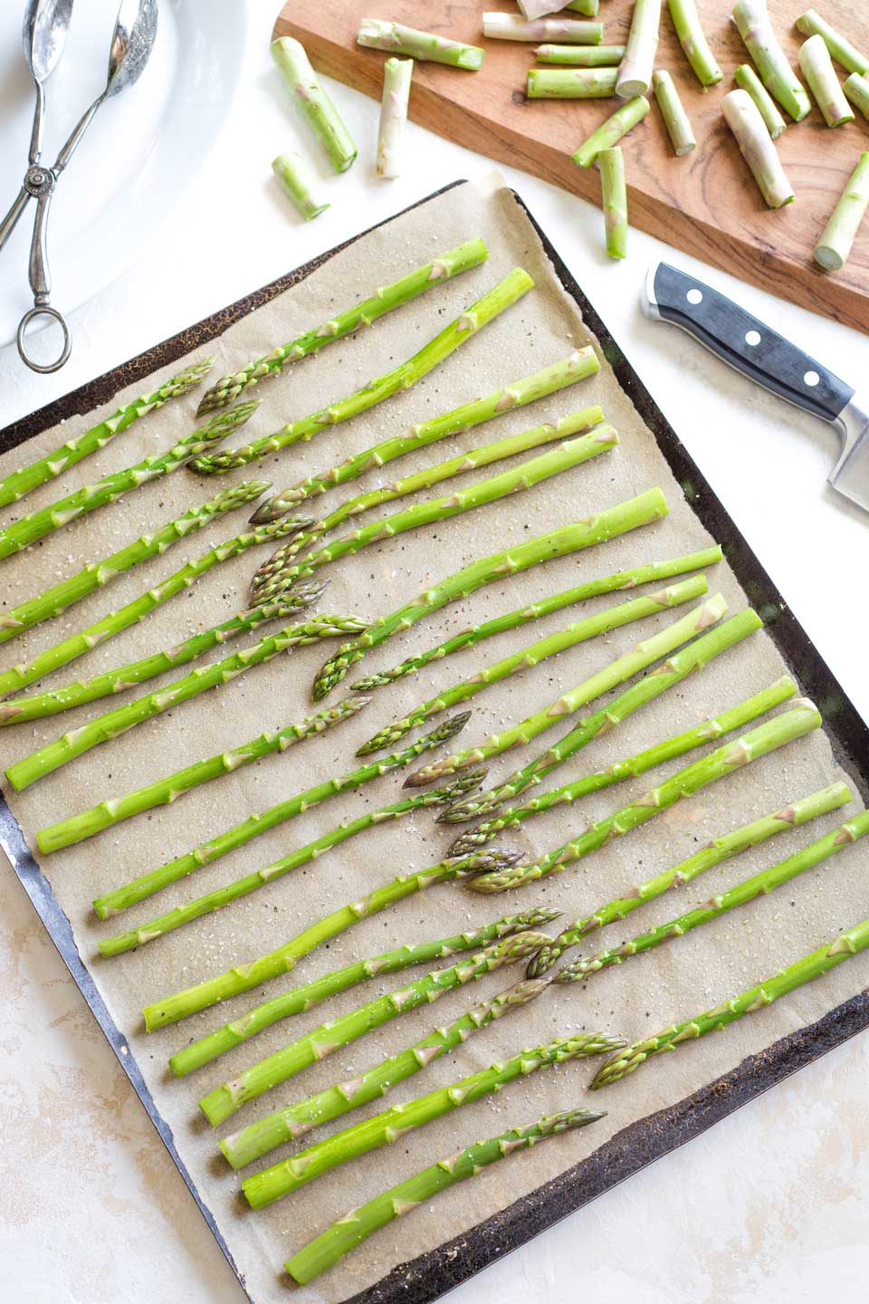 Overhead of a parchment-lined sheet pan ready for the oven, with raw asparagus arranged in a single layer and the discarded ends laying on a nearby cutting board.