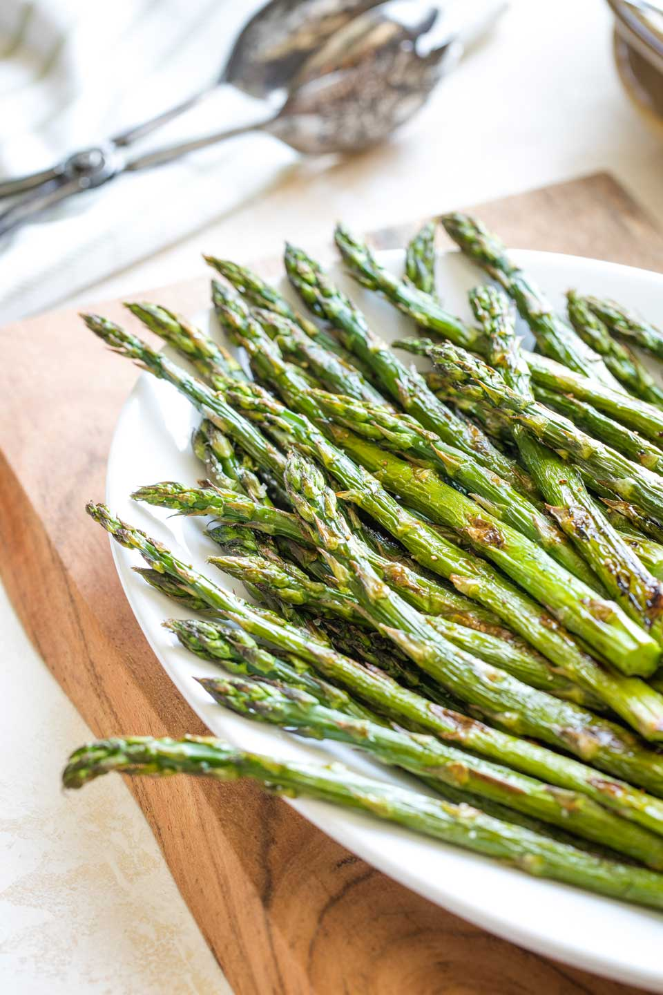 Partial view of the top portion of the roasted asparagus spears after they're out of the oven and pile on a white serving platter that's sitting on a wooden cutting board.