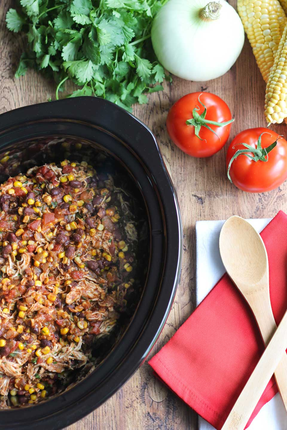 Black slow cooker pot filled with cooked chicken and other ingredients.