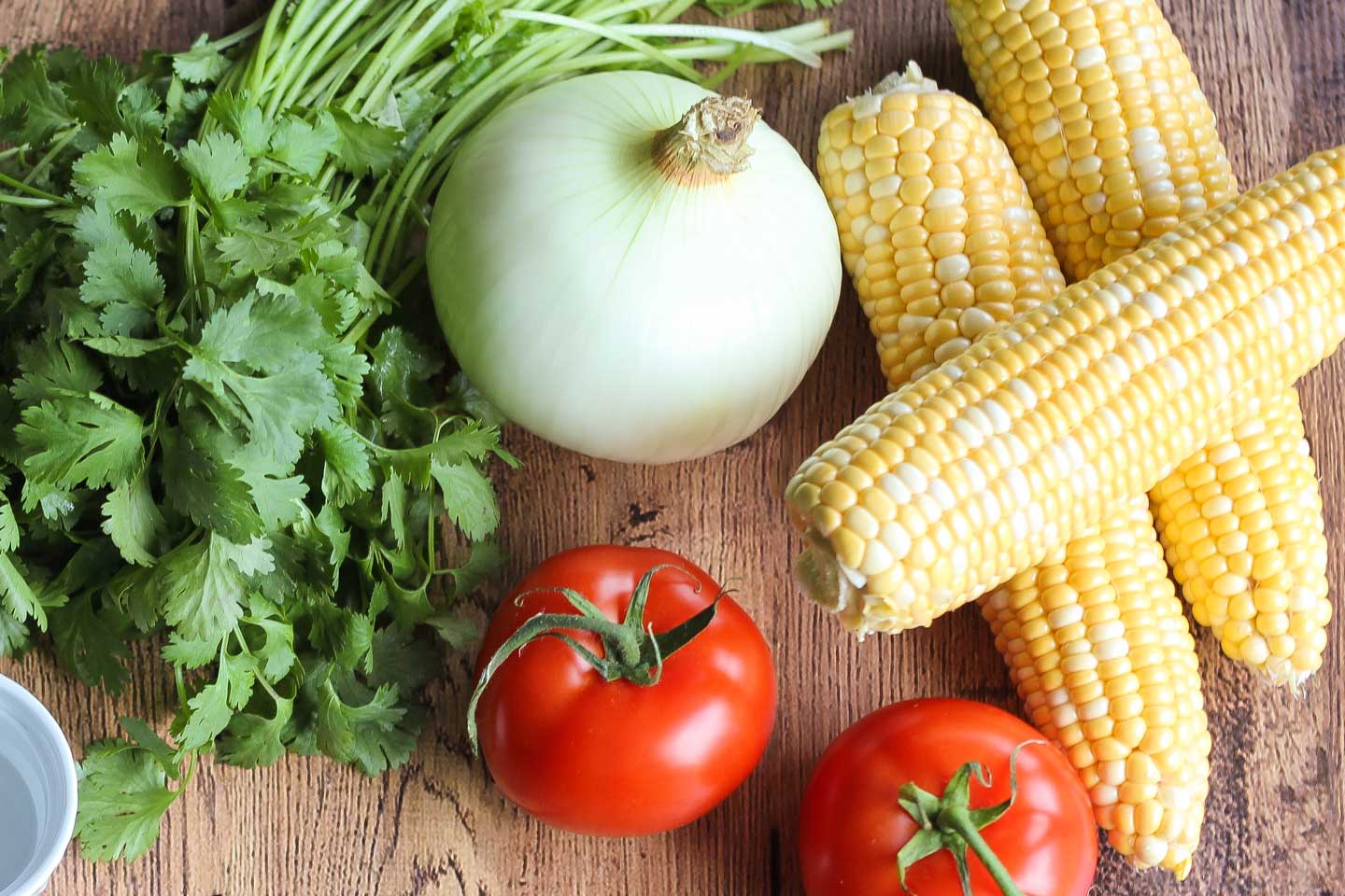 Ingredient photo with a table full of fresh corn, tomatoes, onion, and cilantro.