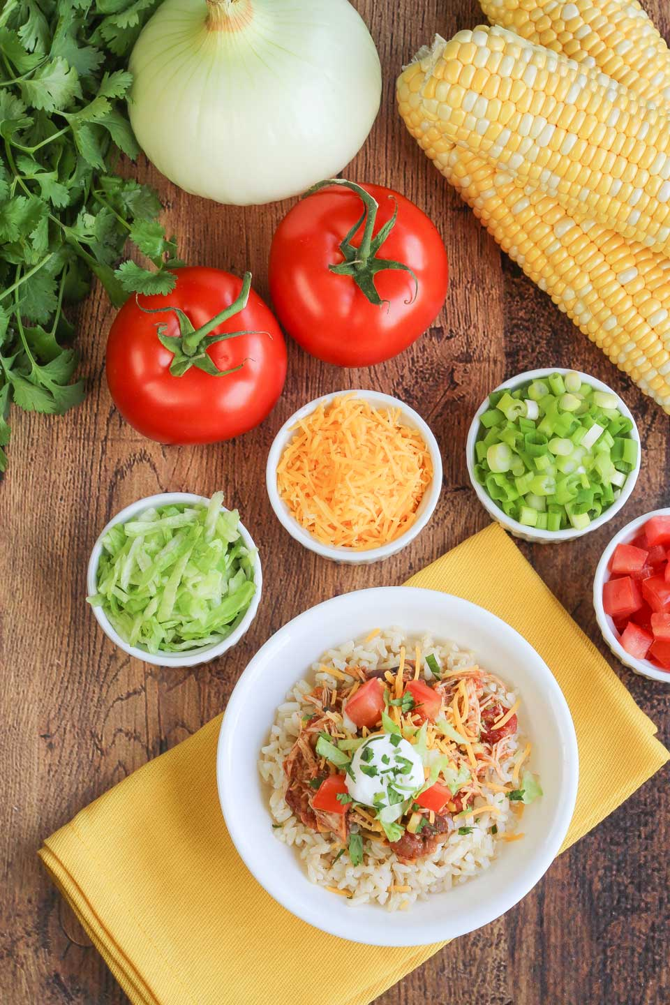 Overhead table spread featuring a central bowl filled with slow cooker chicken on a yellow napkin surrounded by burrito bowl toppings.