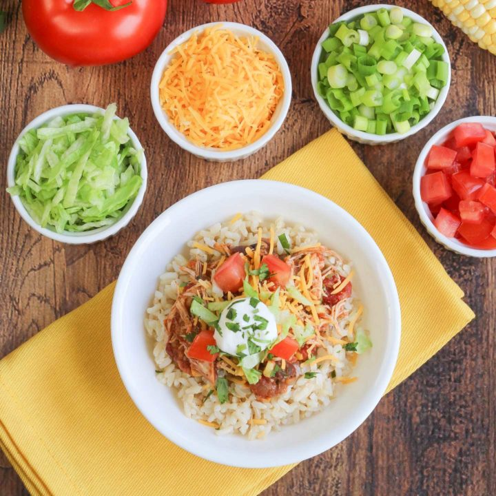 Large white dish filled with finished burrito bowl recipe and surrounded by smaller white cups of toppings.