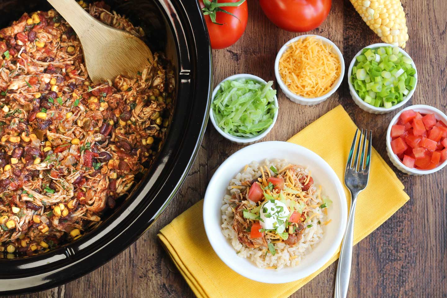 Finished recipe set out on table with full slow cooker, fresh vegetable toppings, and chicken in a bowl.