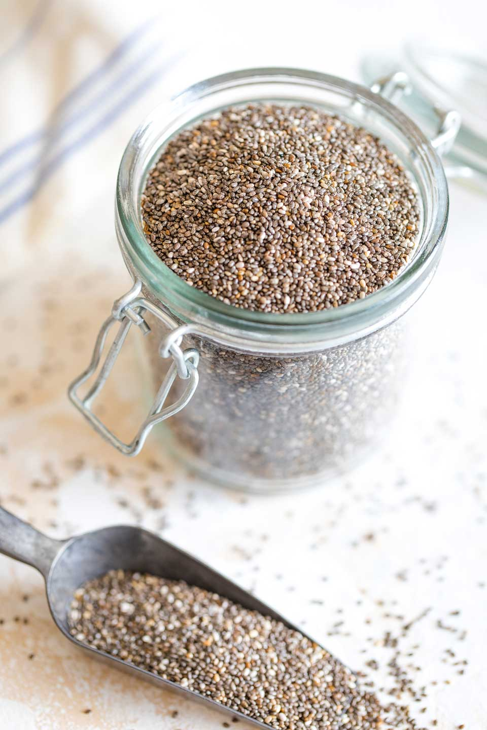 Glass jar of chia seeds with a metal scoop full of seeds laying in front.
