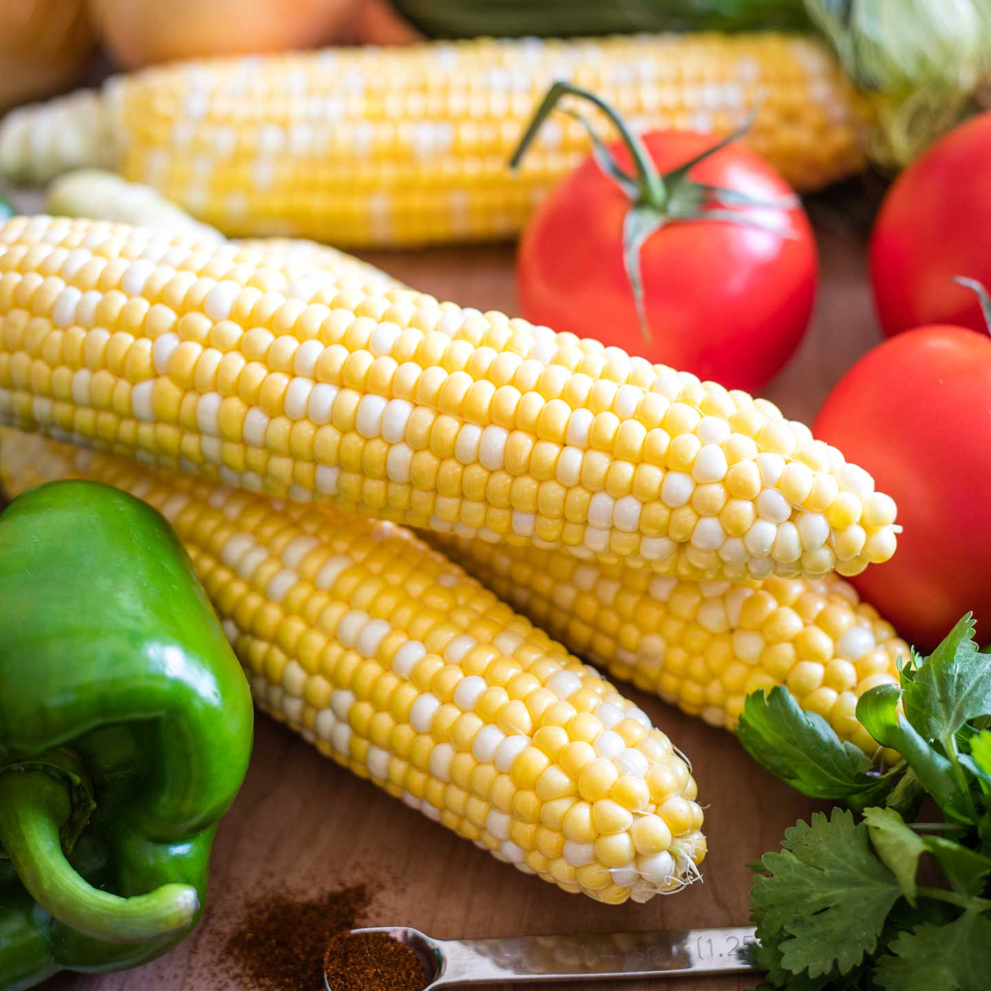 3 husked ears of bicolor corn, surrounded by other salad ingredients.