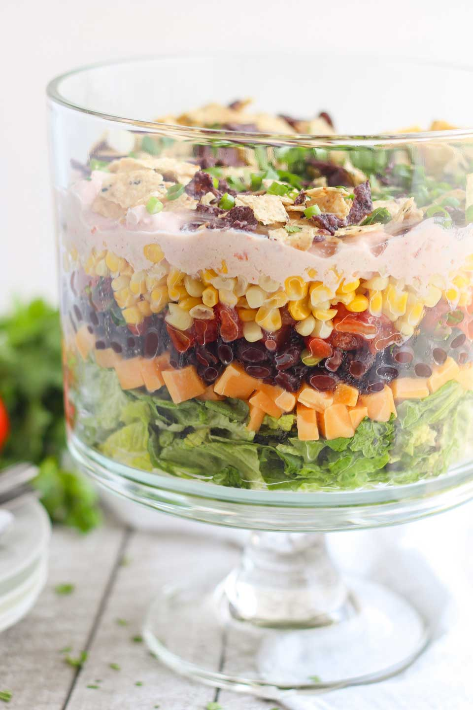 Side view of a clear trifle bowl with layers of salad, corn, tomatoes, cheese, and other Mexican ingredients.