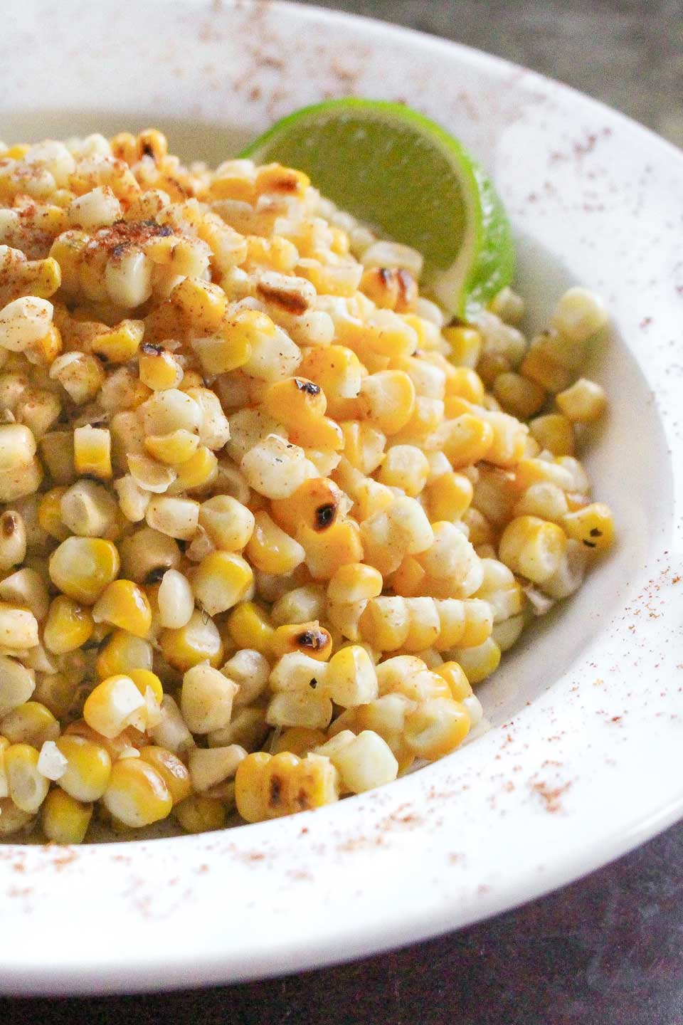 The right half of a rimmed white bowl full of grilled corn salad, sprinkled with spice and garnished with a lime wedge.