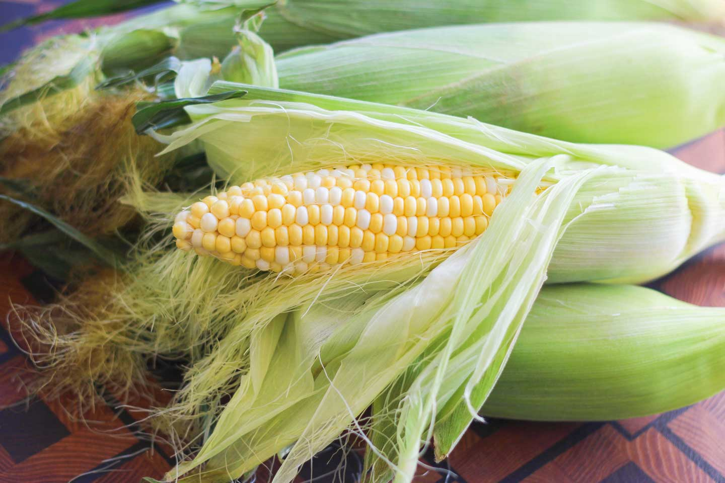 Several ears of fresh corn, still in the husks, with one ear peeled open to reveal the kernels.