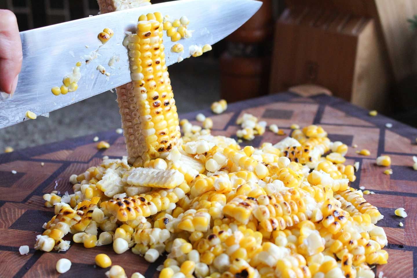 Closeup of a chef's knife cutting grilled corn off a cob onto a patterned cutting board.