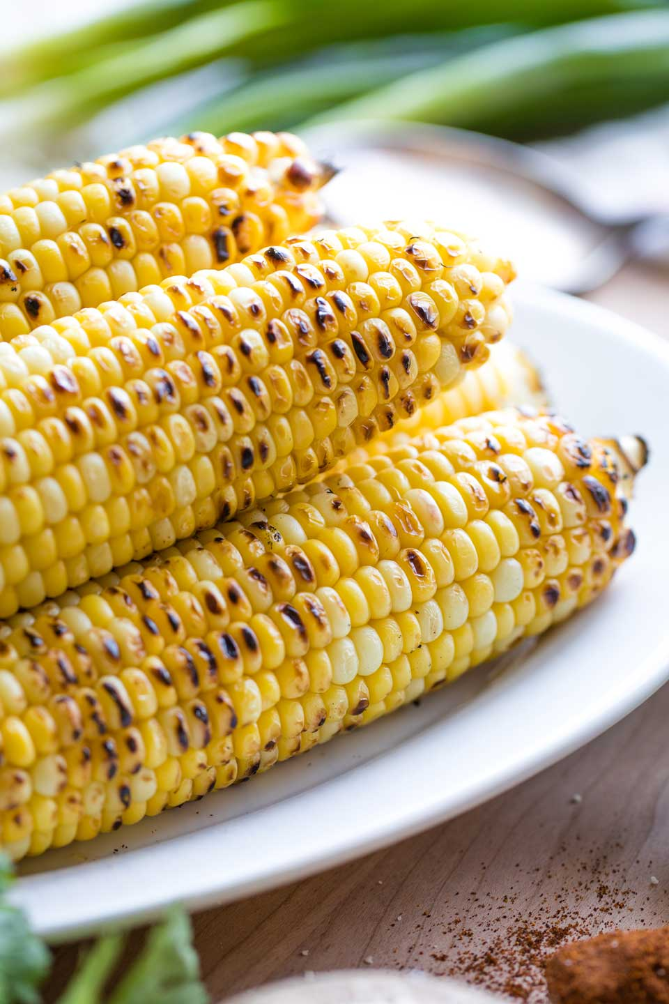 Several ears of grilled corn on a white platter, with other salad ingredients at the phot's edges.