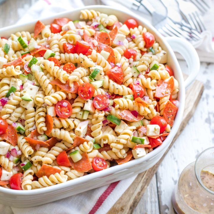 Overhead of a large oval serving dish piled with pasta salad, with a cruet of extra Italian dressing nearby.