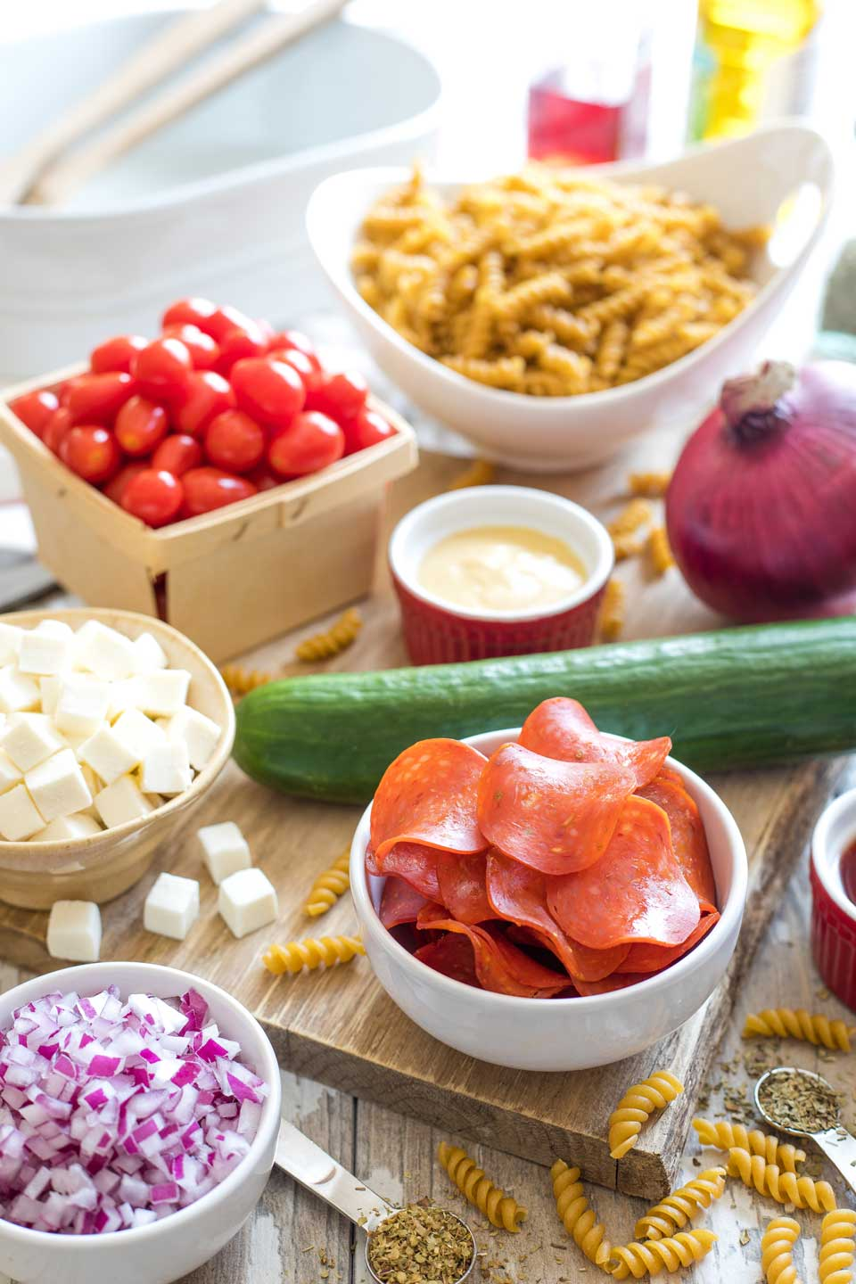 Ingredients for the pasta salad arranged in bowls and spread on a cutting board.