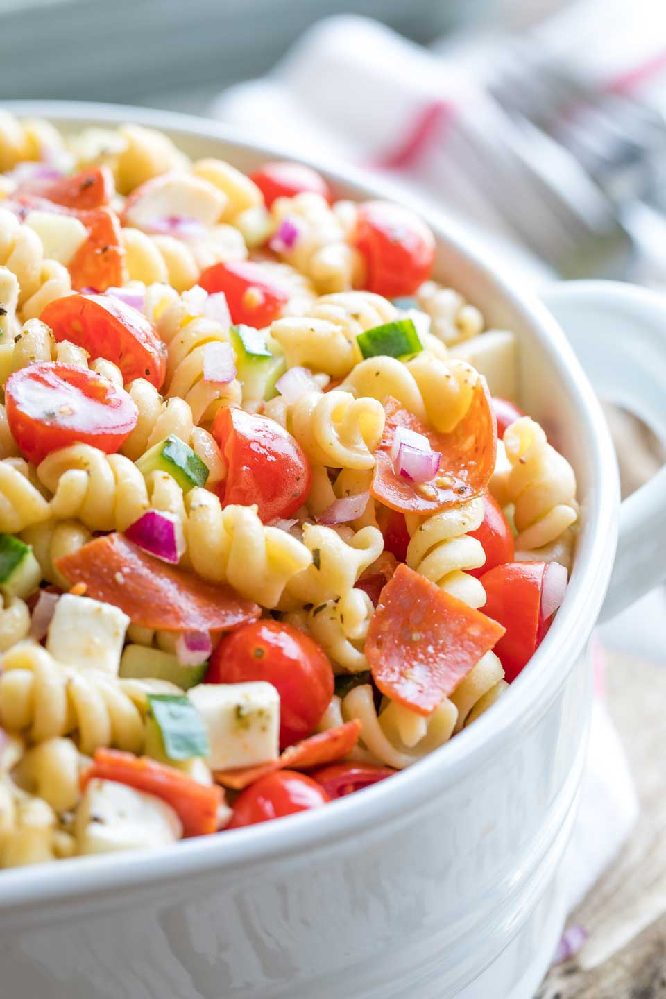 Closeup of the right side of a white serving bowl full of this pasta salad with forks and a red-striped cloth in the background..