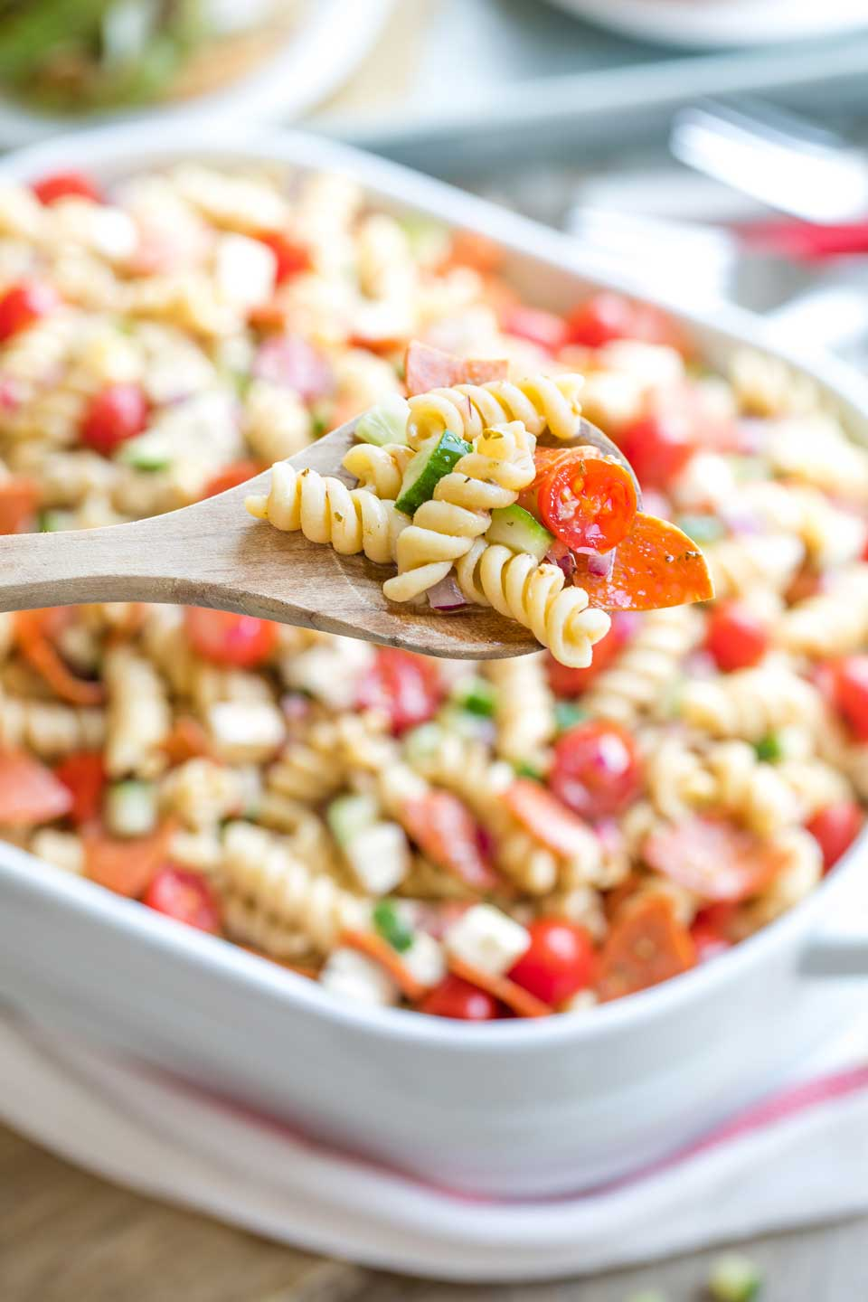 Closeup of a wooden serving spoon holding a scoop of pasta salad with the serving bowl in the background.