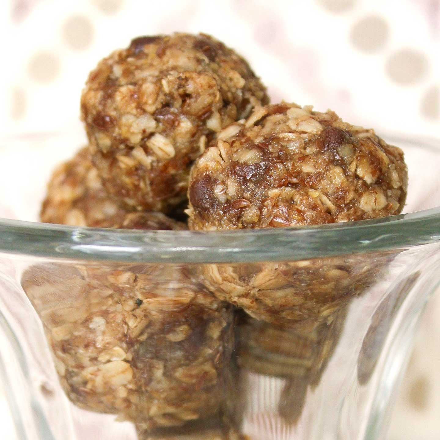 Several energy balls stacked in a tall, clear glass parfait cup.