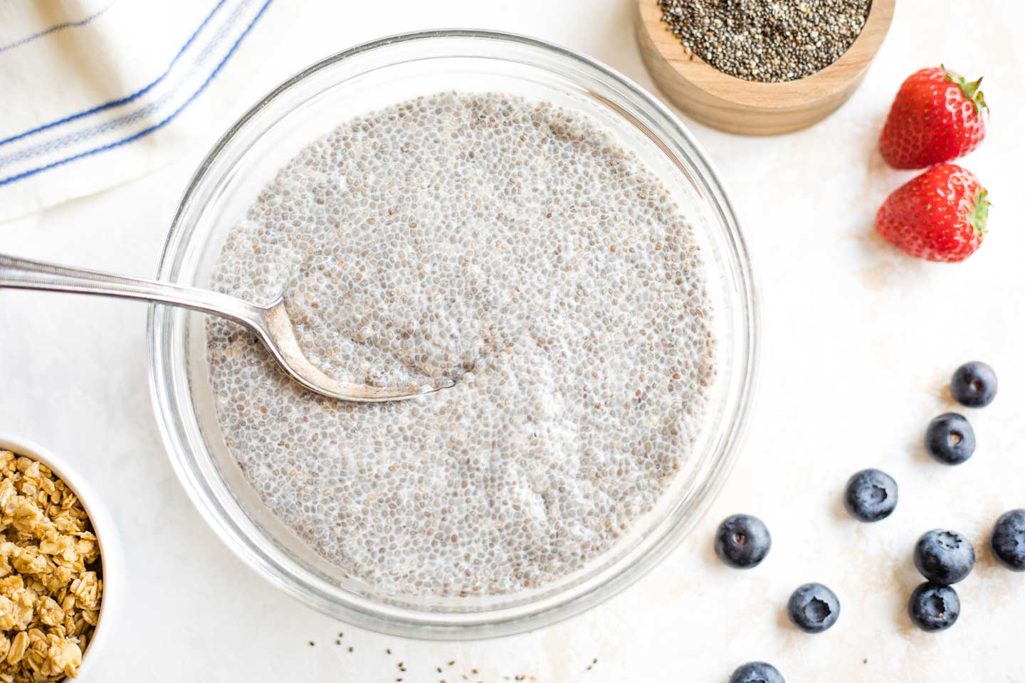 Set chia pudding after overnight refrigeration, with mix-ins like berries and granola nearby.
