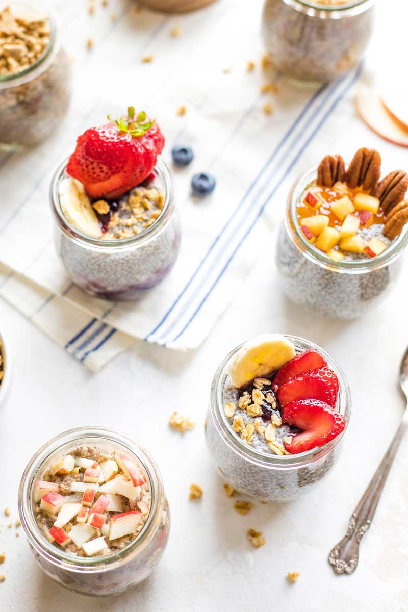 Pinnable image of several pre-portioned jars of Overnight Chia Pudding with different toppings.