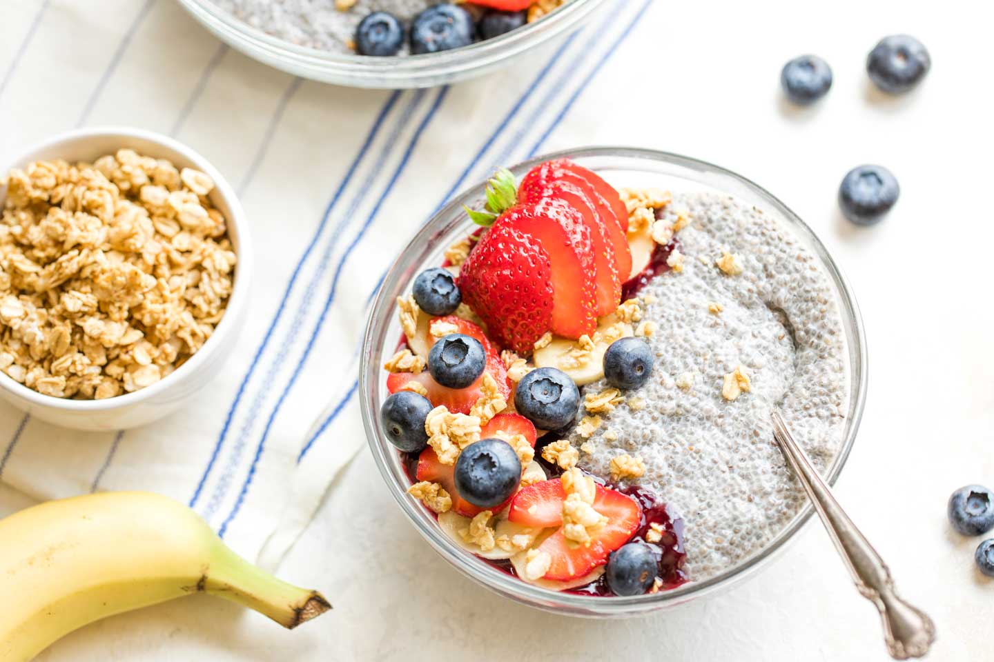 Serving idea showing a little bowl of chia pudding topped with blueberries, strawberries and granola.