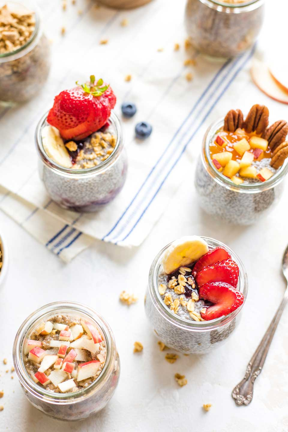 Overhead of several small jars with different chia pudding flavor combos and toppings.