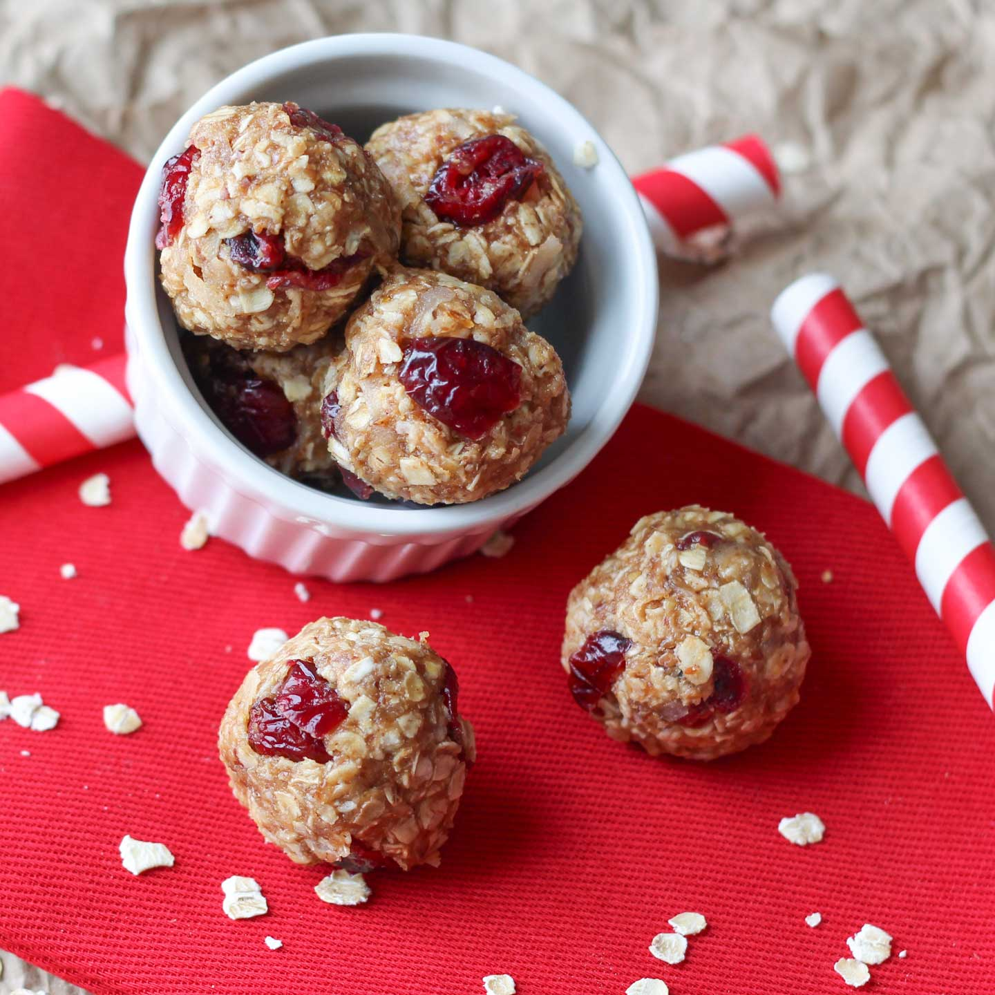 A little white bowl with 4 energy balls displayed, tilted on striped paper straws on red cloth, with 2 more balls in front.