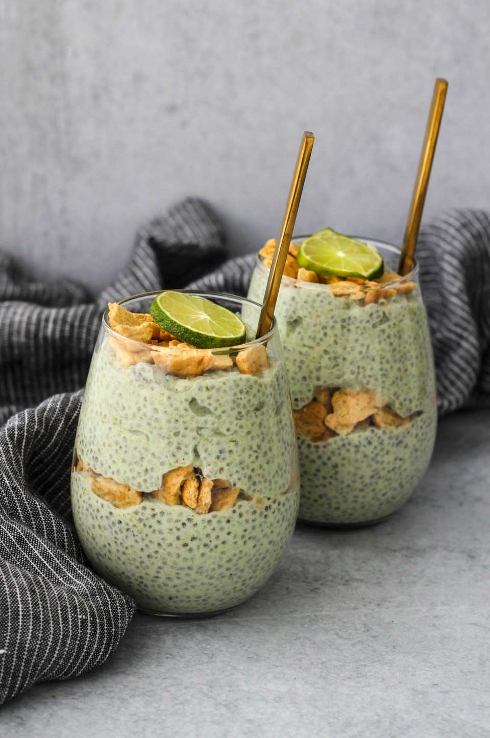 Two stemless glasses showing alternating layers of the chia pudding and broken graham crackers, with lime slices on top and gold spoons.
