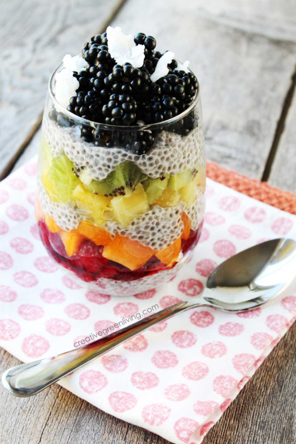 Glass with layers of chia pudding and rainbow-colored fruits, sitting on a pink polka-dot napkin next to a spoon.