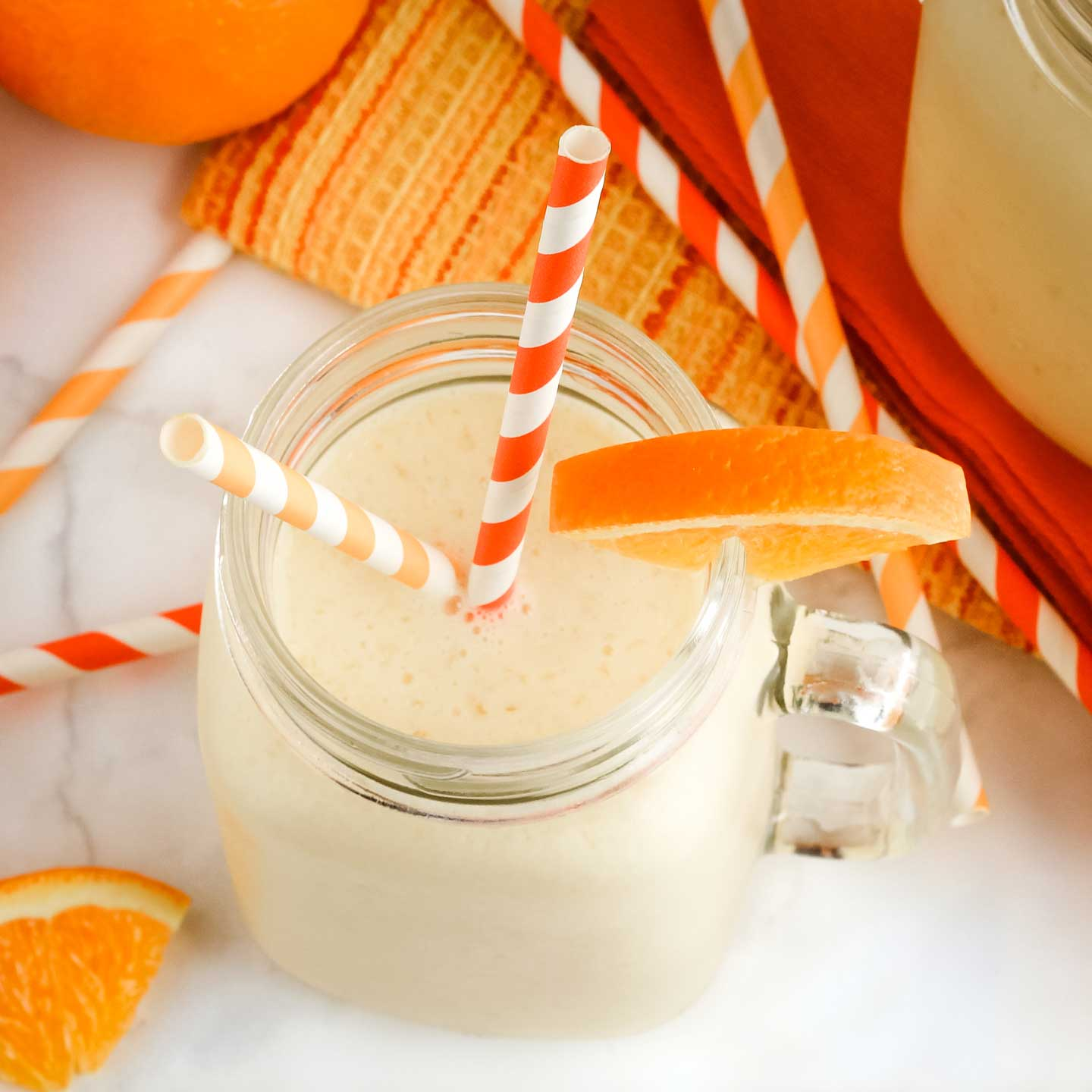Finished smoothie in a clear glass mug with two striped orange straws and a wedge of orange on the rim.