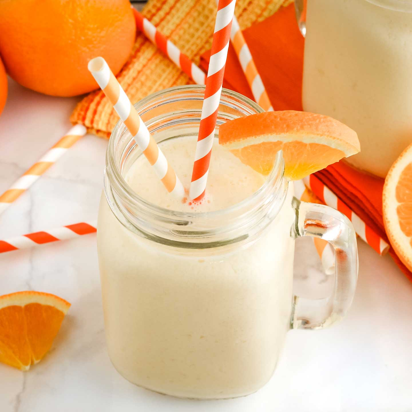 Side view of smoothie in a glass, with a sceond visible behind it, surrounded by oranges and striped straws.
