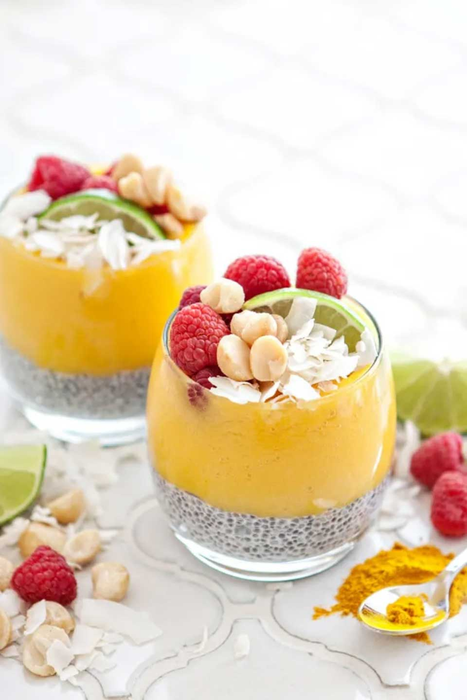 Two glasses layered with chia pudding and fruit puree, garnished with raspberres, coconut, macadamias and lime wedges.
