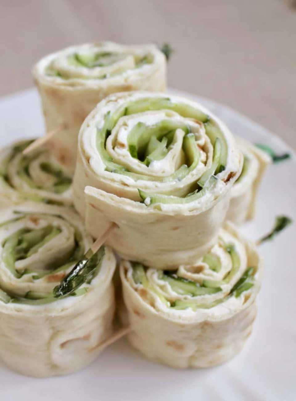 Two-tier stack of 6 sandwiches skewered with green picks on a white plate.