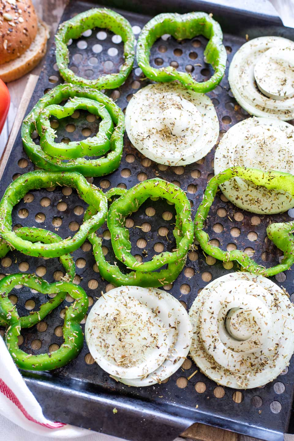 Raw peppers and onions coated in Italian seasoning, laid out on grill pan.