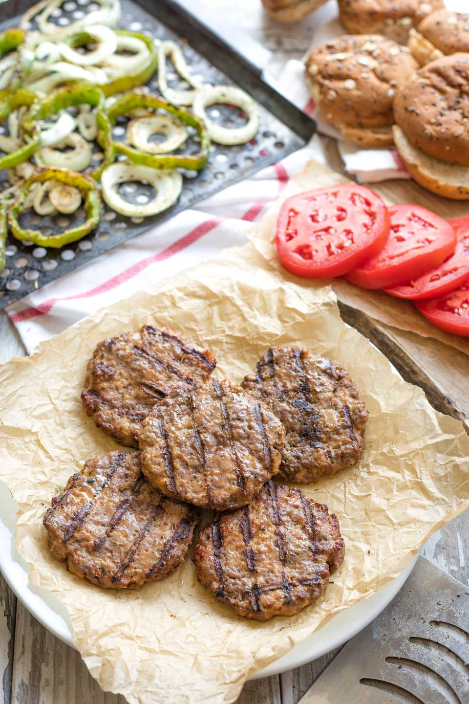 Five grilled hamburgers stacked on a plate with buns and Italian veggie toppings nearby.